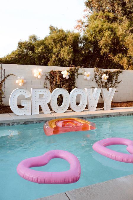 Retro, hippie bachelorette!  Groovy letters were from @desertglowco - balloons & floats are linked!  #liketkit  @shop.ltk   #LTKswim #LTKwedding #LTKunder100