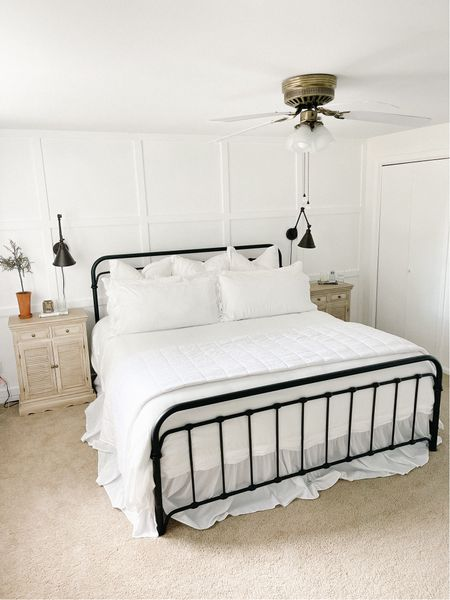 Farmhouse bedroom with white bedding and distressed shutter nightstands    #LTKSeasonal #LTKhome