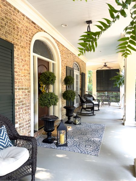 Front porch decor with rockers, outdoor rugs and gorgeous faux topiaries!   #LTKhome #LTKstyletip #LTKSeasonal