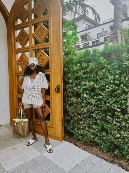 Cream Hole knit sweater, taupe seamless ribbed biker shorts, taupe seamless ribbed sport bra , white knotted slides, palm tree reversible bucket hat and signature print coach tote with neon.   #LTKunder100 #LTKunder50 #LTKtravel