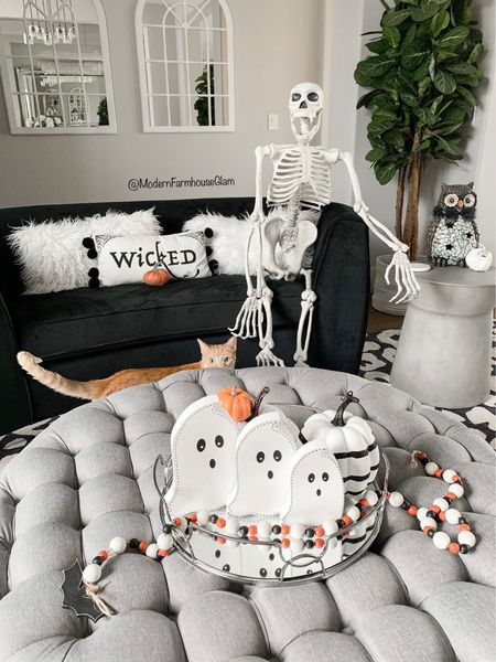 Home Sweet Haunted Home at ModernFarmhouseGlam life-size skeleton, Halloween decor, fall decor, black velvet couch, tufted ottoman, concrete accent tables, and tables, leopard print rug, neutral area rug, furniture, home decor  Wooden ghosts, wicked pillow and Halloween beaded garland can be found on www.modernfarmhouseglam.com in the Glam Girl Fall & Halloween Shop  #LTKhome #LTKHoliday #LTKSeasonal