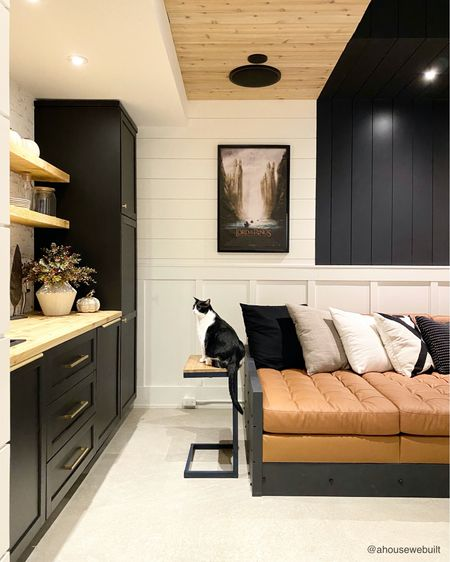 """In our basement theater room, we built a kitchenette snack bar off to the side with a sink, dishwasher, and mini fridge. In contrast to our main upstairs white-toned kitchen, we decided to go dark down here and contrast it with natural wood and brick to give it a cozy, movie room vibe. The """"sofa pit"""" that you can see part of here extends the whole length of the room and the extra deep seating means that everyone gets to put their feet up and snuggle down in a comfy spot. Details and tutorials are on our website's """"Theater Room"""" page. (Cat cameo by Matcha) — Shop your screenshot of this pic with theShop.LTKapp"""