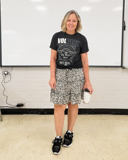 Casual everyday teacher mom outfit featuring a Volbeat graphic band rock tee, boho floral tiered mini midi skirt, and black Reebok Classics nylon sneakers. #tieredskirt #ruffleskirt #boho #teacher #mom #bandtee #graphictee #casual #skirt #miniskirt #midiskirt http://liketk.it/3mwbj @liketoknow.it #liketkit