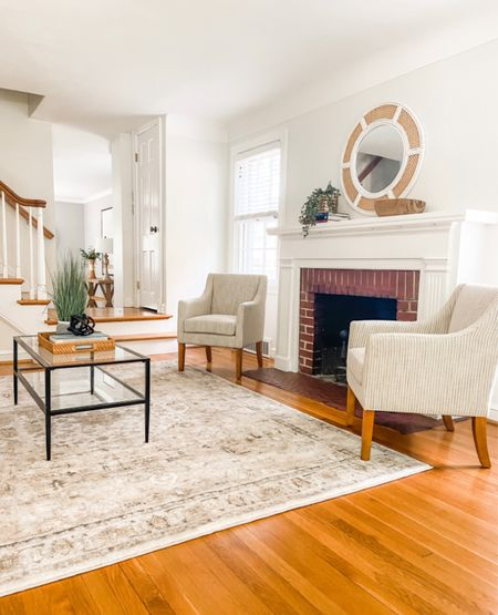 Neutral accent chairs flanking the fireplace in this cozy living room.  Living room decor, home decor, accent chairs, black and glass coffee table, accent furniture   #LTKhome