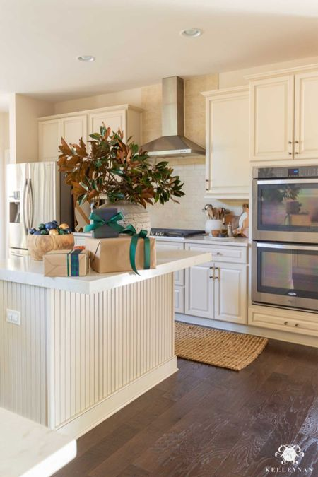 The kitchen island is a great place to style for Christmas. Home decor kitchen decor Christmas decor magnolia branch jute runner cream kitchen cement vase black watch plaid  #LTKSeasonal #LTKHoliday #LTKstyletip