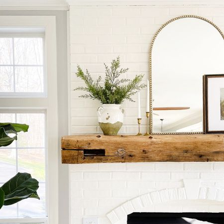 White painted brick with wood fireplace mantle and Pottery Barn vase with greenery and a gold arched mirror #potterybarn #fireplace #goldmirror #familyroom   #StayHomeWithLTK #LTKhome #LTKstyletip