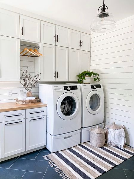 Farmhouse laundry room. Laundry room decor. White shiplap white cabinets scatter rugs baskets hamper with lid trays wood hangers washer and dryer vases and vessels fall florals  #LTKSeasonal #LTKunder50 #LTKhome