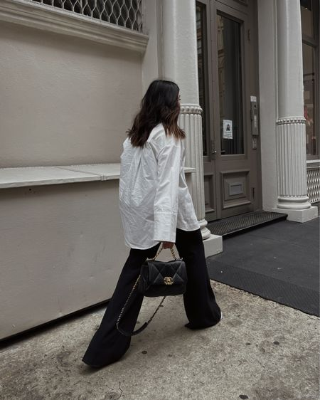 City outfit with white blouse, wide leg pants, and Chanel 19.