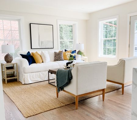 Beautiful neutral living room with a white slipcovered sofa and a wood and metal coffee table.  Living room decor, white sofa, neutral art, cement lamps, home decor, coastal decor, wood coffee table    #LTKhome