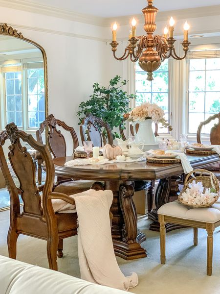 Create a French Country feel in your dining room with these show stoppers! An oversized gold mirror, splatback carved chairs and a tufted bench bring some European charm in this dining room! A cozy (Target) throw, a Muslin runner and basket of florals bring the cozy cottage feel!   Anthro Mirror Dining chairs  Dining table Ironstone Pitcher Tufted Bench  Muslin Throw Blanket Pumpkin decor     #LTKhome #LTKSeasonal #LTKunder50
