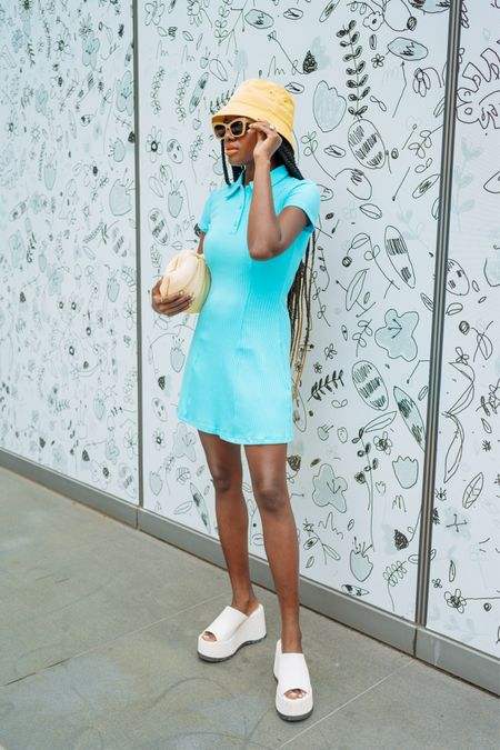Summer vacation outfit. Tennis dress in turquoise, white platform mules, tan yellow bucket hat tan sunglasses.   #LTKtravel #LTKunder50 #LTKunder100