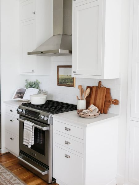 Kitchen decor for summer. Im loving the wood cutting boards with the white cabinets. Etsy artwork is framed in an Amazon frame. The neutral dish towels bring just enough pattern to the space.    You can instantly shop my looks by following me on the LIKEtoKNOW.it shopping app http://liketk.it/3jLCe #liketkit @liketoknow.it