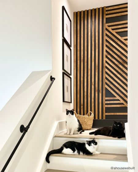 Our slat wall was such a fun way to add character to this stair landing but you have to watch your step because our rescue kitties love to get underfoot! We've shared the tutorial for how to do a slat accent wall on our website if you're interested. We also loved these square gallery wall frames so much that we decided to use the larger version of them again in another part of our home so I'll share pics of that soon. I just love how simple and minimal they are! (Cat cameos by Matcha, Chai & Nyx) — Shop your screenshot of this pic with theShop.LTKapp.