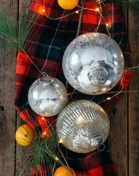 This red plaid scarf, mercury glass ornaments, and twinkle light tablescape makes me smile. The fresh greenery and oranges take it over the top!   #StayHomeWithLTK #LTKhome #LTKstyletip