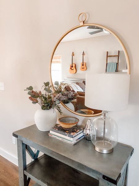 Entryway decor for 2021 ❄️  • thrifted + upcycled vase • floral arrangement using faux eucalyptus, pine cone picks, + real greenery • stack of magazines + books • diffuser • lamp  #homedecor #entrywaydecor #moderncottage #targetfinds #targethomedecor #targetdecor #tablestyling #roundgoldmirror #goldmirror #favoritebooks  #LTKhome #StayHomeWithLTK #LTKNewYear