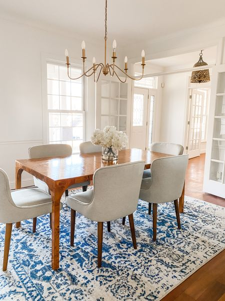 Simple brass chandelier over this traditional burl dining table with white upholstered chairs.  Dining room decor, home decor, dining table, white chairs, upholstered chairs, burl furniture, chandelier, dining room ideas, blue and white rug  #LTKhome