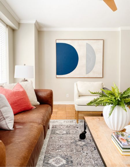 Beautiful leather sofa paired with white accent chairs and bold artwork.  Living room decor, leather couch, neutral accent chairs, abstract art, home decor  #LTKhome
