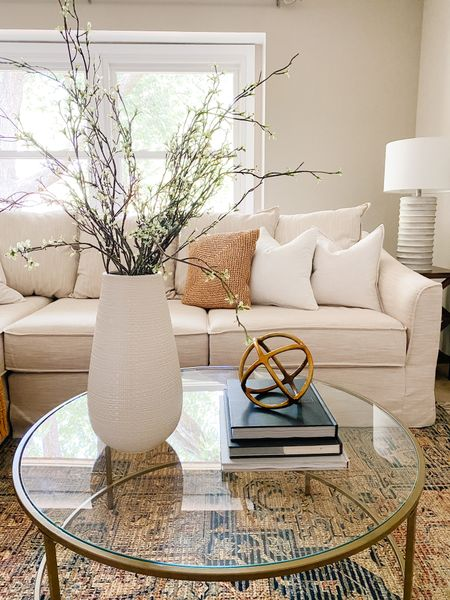 A white vase with faux branches looks clean and simple on this round glass coffee table.  Living room decor, coffee table style, faux branches, home decor ideas, glass table  #LTKhome