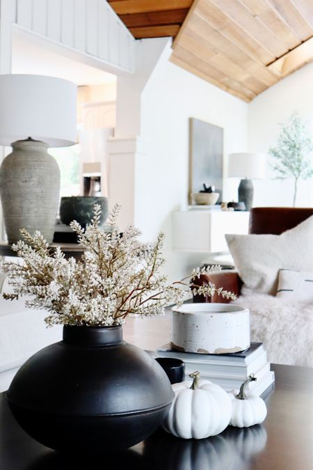 Here's how I do neutral fall decor in our home!  I love the different hues of creams and grays with pops of black. As Halloween gets closer I'll throw in some orange, but for now, I'm loving this look!   Faux fall flowers, black iron pot, leather recliner, sheepskin, candles, cozy blankets, squishy pillows, ambient lighting.   #LTKSeasonal #LTKstyletip #LTKhome