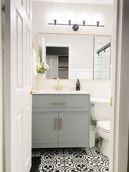 Black and white tile add fun to this small bathroom update.  Gray vanity, bathroom reno, bathroom decor, decorative floor tile, gold hardware  #LTKhome