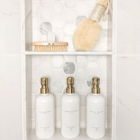 """One of our favorite features of our newly renovated bathroom is the shower niche and these beautiful dispensers, which we use for shampoo, conditioner and body wash! They completely streamline and elevate the look of our bathroom! I chose the plastic bottles for our shower so we don't have to worry about them breaking if they are dropped on our marble shower floor, but also linking glass bottles that I love for the kitchen!  Marble niche tile is called """"Africa Tempesta Polished Palatine"""" from The Tile Shop. - Bathroom ideas, shower niche, shampoo bottles, body wash bottles, coastal bathroom accessories, bathroom accessories, shower bottles, bathroom decor, body brushes, soap dispensers, soap bottle tray, plastic soap dispensers, glass soap dispensers, glass soap bottles, plastic soap bottles   #LTKstyletip #LTKfamily #LTKhome"""
