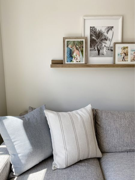 """Hello everyone! I finally swapped out my winter art on our floating shelf now that spring is in full bloom. Our wedding photography by @rebeccaarthurs is so beautiful  and transports us back to Maui 🤍 I linked the floating shelf and my pillow covers + all time fav insert for you. The insert is down-free but still gives a great """"chop"""" if that's your thing. The covers both have zippers making them easy to switch out. The blue-gray one is the prettiest light blue color I have found to date! Happy Monday!   #LTKhome"""