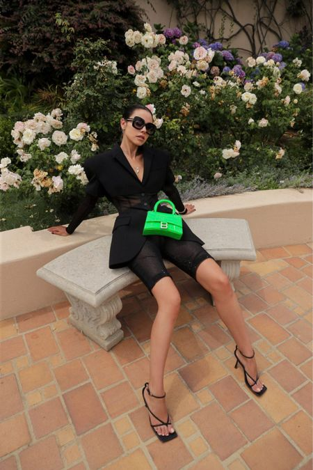 Super chic all black outfit with a pop of color courtesy of this neon green Balenciaga mini bag. Obsessed with this super structured black blazer paired with embellished biker shorts   #LTKitbag #LTKstyletip #LTKshoecrush