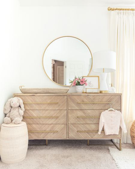 """Eliza's nursery dresser in the gray finish is in stock and on sale; Eliza's round brass mirror is also a sweet deal (she has the 36"""" brass version but there's several sizes and finishes available ;)). Shop these here or head to the latest post on KelleyNan.com for all the sale details, promo codes and details! http://liketk.it/3gnK4 #ltkkids #liketkit @liketoknow.it #LTKbaby #LTKsalealert @liketoknow.it.home #LTKhome nursery decor bedroom dresser round mirror large mirror modern dresser master bedroom decor home decor woven hamper baby room ideas baby girl nursery design inspo nursery inspo table lamp"""