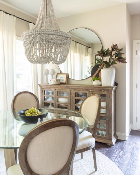 My fall look in the breakfast nook is neutral with pops of green. Home decor fall decor faux magnolia artichoke beaded chandelier dining chair black bowl round mirror ritva curtains   #LTKhome #LTKSeasonal #LTKstyletip