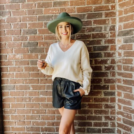 """Could absolutely LIVE in this look! Nothing says, """"fall is here"""" like a hat, sweater, and leather shorts combo! @Kirundo_Chic hooked a sister up with this adorable cream sweater, with a frill detail on the sleeve. I am so pumped to style this into the winter season as well. Today I've thrown on an older pair of faux leather shorts, my new Target hat & a pair of booties to complete the #ootd. Everything is linked in the LTK app for y'all!"""