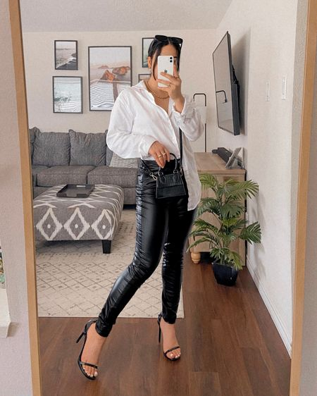 LOOK 2: How To Style a White Button Down - Here I went for an edgy look by styling the blouse with a pair of black faux leather pants and black accessories to match. These strappy stilettos are so sexy, and this mini bag is very on trend.    Follow me on the LIKEtoKNOW.it shopping app to get the product details for this look and others    http://liketk.it/3gDTY #liketkit @liketoknow.it #LTKitbag #LTKshoecrush #LTKunder100