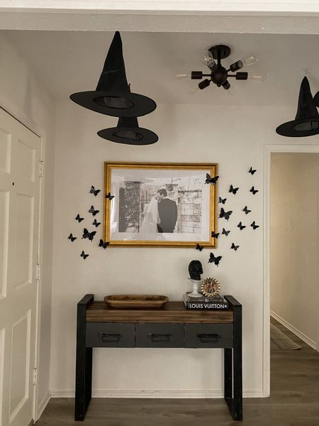 halloween decor for the entryway 🖤 love the black butterflies for something different! Added fun floating hats too and my skull candle is so vibey. Console table is 10 years old! can't link   #LTKHoliday #LTKhome #LTKSeasonal