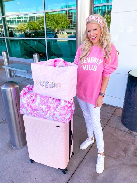 Beverly Hills pink oversized sweatshirt size L.  High waisted white jeans  White sneakers run large - size down 1/2 size  Stoney clover duffel bag Stoney clover tote bag with rainbow gingham letters and Barbie patches  Stoney clover and Lele pink watermelon headband  Kendra Scott gold necklace  Gold target hoops  Apple Watch band   Travel outfit, fall outfit, sweatshirt, Stoney clover lane, travel style  #LTKunder100 #LTKitbag #LTKtravel