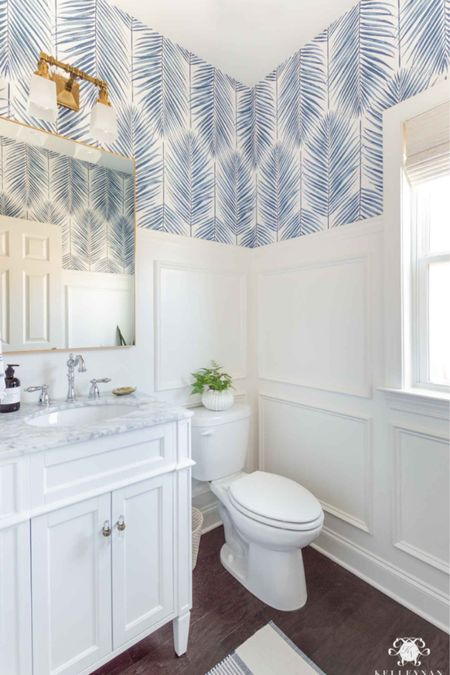 Our coastal powder room features picture frame moulding and blue and white wallpaper. Home decor small vanity brass sconce   #LTKstyletip #LTKhome