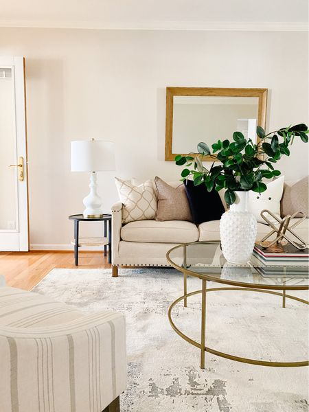 Beautiful neutral living room with a nailhead sofa and a glass round coffee table.  Living room furniture, living room decor, sofa, upholstered couch, coffee table, accent furniture, side tables   #LTKhome