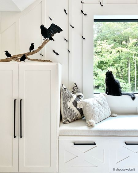 """On our bedroom's window seat, Nyx is eyeing up my Halloween bats and birds! We built this bench and cabinetry to provide storage and seating for our bedroom. This is super functional for storing extra pillows and linens, plus it adds in functional seating space too without needing to add any furniture pieces. We've shared the whole process of how we built it on our website's """"Tutorials"""" menu if you're interested to see how it came together. — Shop your screenshot of this pic with theShop.LTK app"""