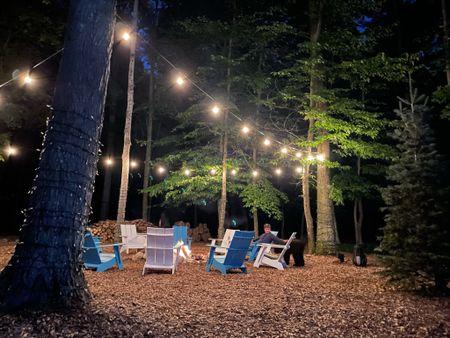 New backyard lighting Bistro lights Adirondack chairs  loll designs #lollon  Bonfire pit Backyard   #LTKhome #LTKSeasonal