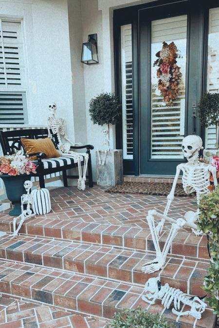 Halloween fall front porch. Found some outdoor greenery wreaths and topiaries on sale! Things sell fast here tho! Skeleton bench patio outdoor decor   #LTKhome #LTKHoliday #LTKSeasonal