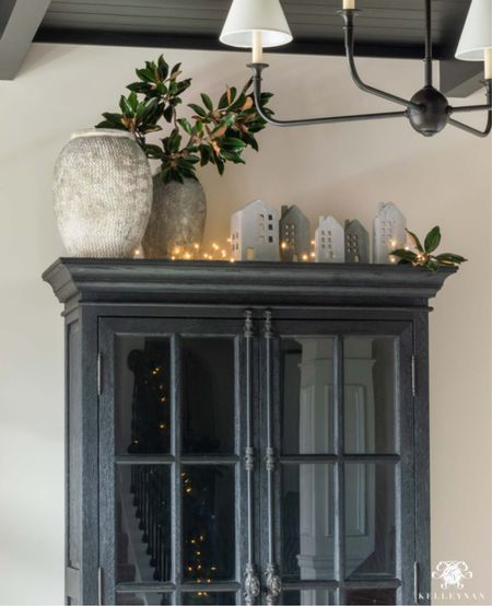 This Christmas village adds a whimsical touch on our black curio cabinet. Home decor Christmas decor living room decor iron chandelier cement vase twinkle lights  #LTKunder50 #LTKHoliday #LTKSeasonal