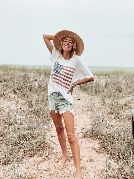 Fourth of July outfit ideas 4th of July flag tee Revolve outfit ideas Abercrombie high rise denim shorts Straw hat Beach outfits   #LTKstyletip #LTKSeasonal