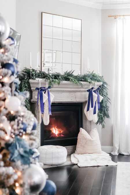 Christmas decor, mantle decor, faux cedar garland, brass decor, taper candle holders, leather pouf ottoman, Barefoot Dreams throw blanket, stockings, panel mirror, living room, sofa, couch, coffee table, ottoman, home decor, Amazon Home finds  #LTKhome
