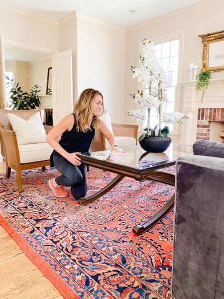 Wiping down the glass coffee table in this stunning living room!  Vintage rug, woven chairs, living room decor, home decor  #LTKhome