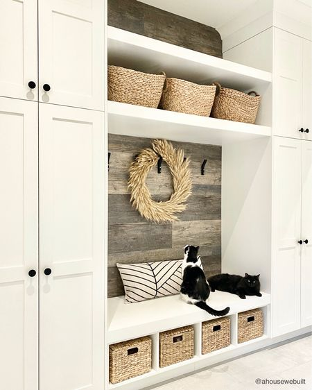 """In our mudroom, we combined different types of storage to make this zone as functional as possible. The black hooks (with the cutest gold detailing if you zoom in!) are of course usually filled with coats and sweaters so we used a waterproof flooring material behind them to give a rustic barn-wood look that would be smooth, wipeable, and easy to clean. We added lots of woven baskets for texture and practicality, and also put in closed storage that can be used in 3 ways (as individual lockers, as hanging coat storage, and as regular shelving) depending on how we configure them. Sources are on our website's """"Mudroom"""" page. (Cat cameos by Chai & Nyx) — Shop your screenshot of this pic with theShop.LTKapp"""