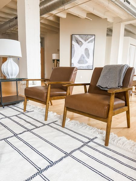 A pair of leather accent chairs in the loft living room.  Leather chairs, mid century modern, living room decor, black and white rug, loft style  #LTKhome