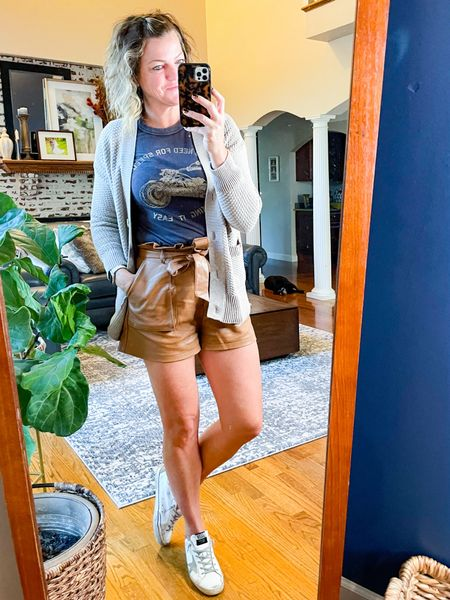 These vegan leather shorts have the cutest paper bag detail. They are high waisted and TTS   This graphic tee is very fitted and cropped. I sized up a size. I could have sized up a couple but it works perfect with high waisted.   This cardigan is sold out in the color but available in an orange and a blue. It is TTS     #LTKSeasonal #LTKstyletip #LTKsalealert