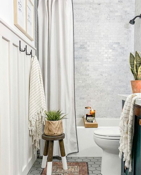 Freshly remodeled modern farmhouse style guest bathroom. Features a handmade vanity with marble top, a rustic wall mirror, matte black faucets, a paint dipped stool with faux greenery in a wooden planter, matte black wall hooks, striped Turkish towels with and DIY board and batten wall treatment. Love the classic shower marble subway tile with a hex floor tile in this coastal bathroom. Bathroom inspo, bathroom cabinet, bathroom decorating, bathroom countertop, bathroom towels, bathroom mirror, bathroom vanities, bathroom hardware, bathroom mirrors, bathroom accessories set, farmhouse decorating, modern design, modern inspiration.  #StayhomewithLTK #LTKsalealert#LTKunder50#LTKstyletip#LTKunder100#ltkfamily#LTKstyletip#LTKunder50#LTKunder100#LTKhome   #LTKstyletip #LTKunder50 #LTKhome