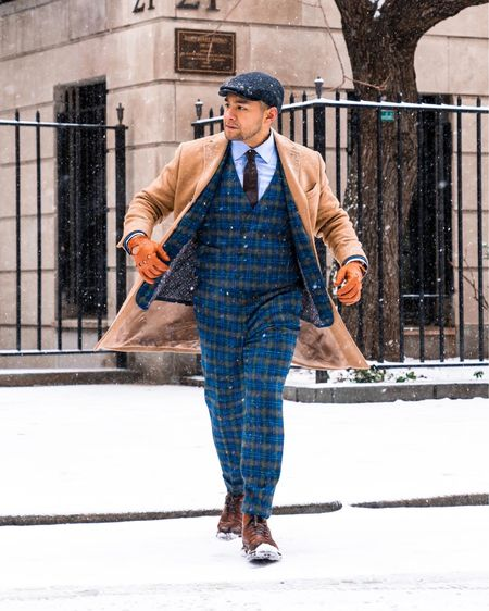 """A modern day peaky blinders on a snow day. If you want to wear boots with your suit, consider thicker fabrics, like tweed, and layering so it balances out with """"heaviness"""" of the boot.   Oh, and button up... unless you are making content.   Top Coat by @petermanningnyc  Watch by @omega  Three Piece Suit by @get_the_drop  Flat Cap by Weavers of Ireland  Boots by @florsheimshoes   Photography by @byhill_   How to style a Camel top coat. Tweed plaid three piece suit. Driving gloves. paddy cap. Boots with a suit. How to wear boots with a suit.   #LTKworkwear #LTKmens"""
