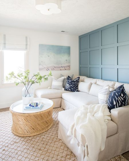 Love the coastal vibes in our den! Items include several colors and patterns of pillows, a glass vase with a white painted bottom filled with faux greenery and an abstract beach wall art. Other items include a slip-covered sectional, a round bamboo coffee table, striped roman shades, a jute area rug and a scalloped flush mount light.   simple decorating, home décor, coastal decor, neutral design, coastal design, family room, game room, media room, den, den inspo, home decor, pottery barn shades, pottery barn sofa, neutral decor, family room decor, family room area rug, rugs on carpet, rug family room, art for home, abstract wall art, serena and lily home décor, serena and lily rugs, serenaandlily coffee table, coffee table decor, family room inspiration, serena and lily pillows, amazon finds, amazon home decor, amazon under 20, target finds targetdoesitagain, targetfanatic, coastal inspiration   #LTKSeasonal #LTKstyletip #LTKunder50 #LTKunder100 #LTKsalealert #LTKhome #LTKfamily #LTKstyletip #LTKunder50 #LTKhome