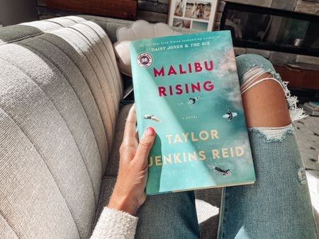 Malibu rising a novel by Taylor Jenkins Reid Suspenseful story about siblings on the coast of Malibu   Best skinny jeans from Abercrombie high rise jean legging  Cardigan and cozy vibes for reading   #LTKSeasonal #LTKhome