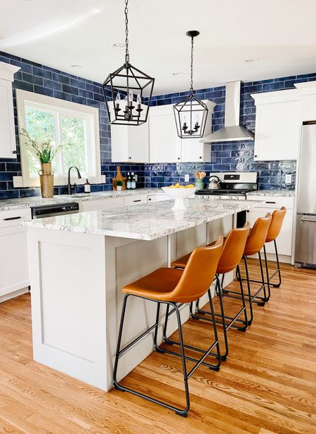 Beautiful blue tile in this modern kitchen with leather counter stools and lantern pendants.    #LTKhome